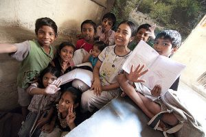 children in India launghing with books in their hands