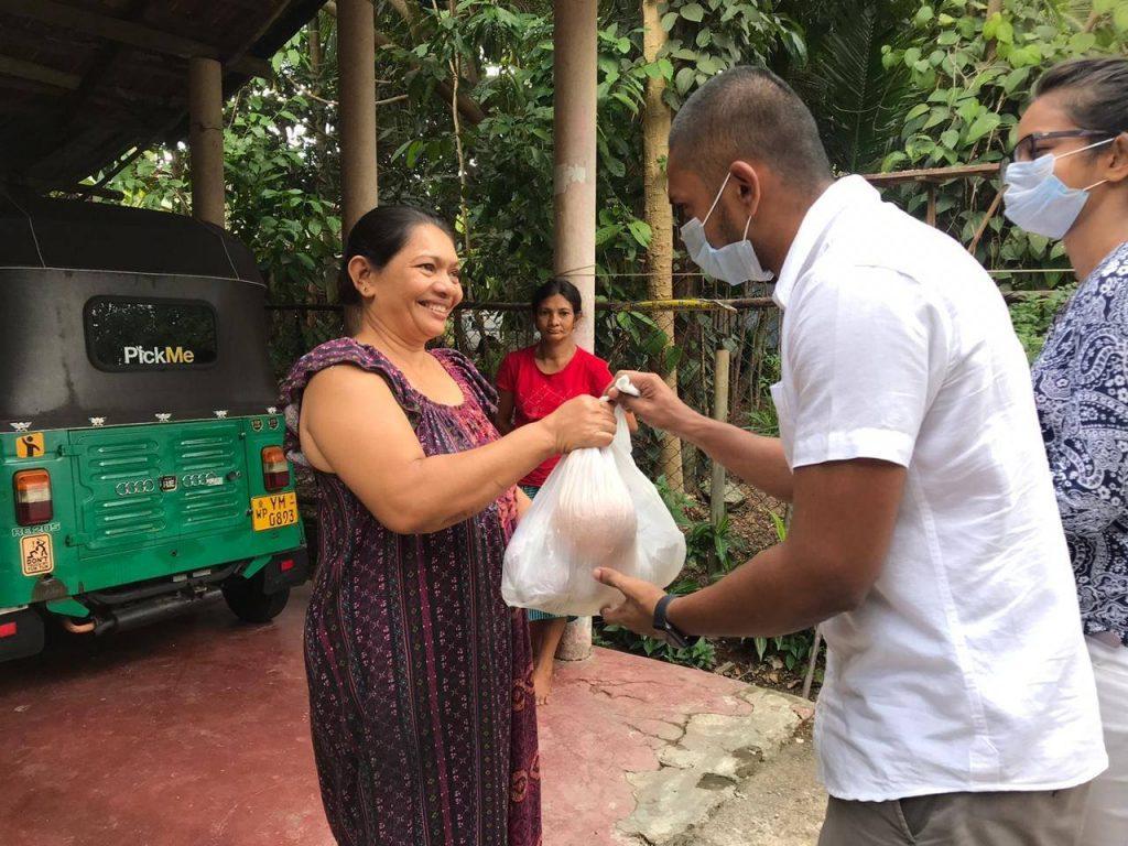 United2Care volunteers present a bag of groceries