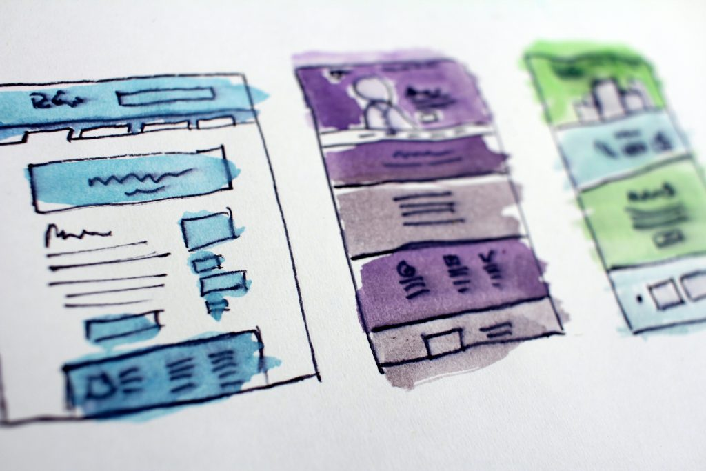 A purple and blue wireframe sketch of a website, drawn on paper