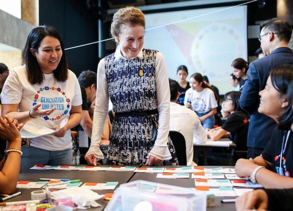 Image of the UNICEF Executive Director Henrietta H. Fore with young people at a table
