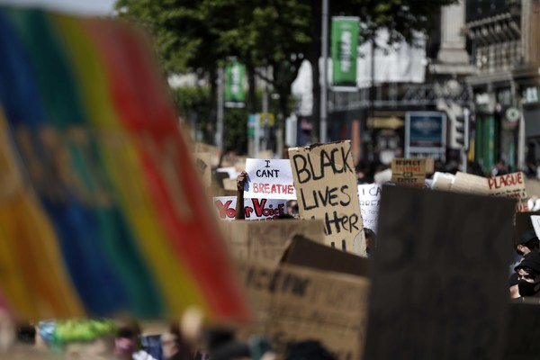 Image of Black Lives Matter protest featuring signs with the rainbow flag.
