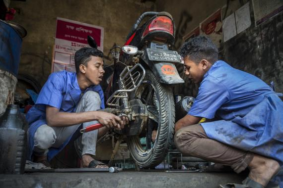 Image of youth repairing a motorcycle