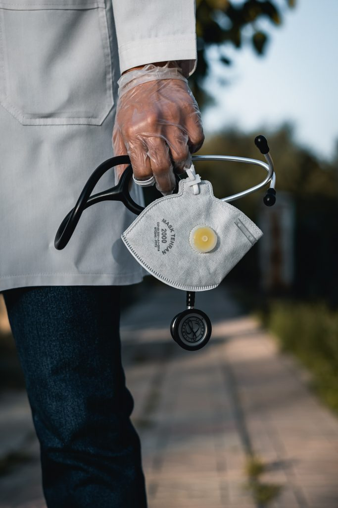 An image of a doctor holding a stethoscope and a mask.
