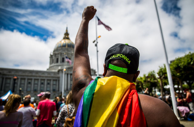 Black man with a rainbow flag raises his fist