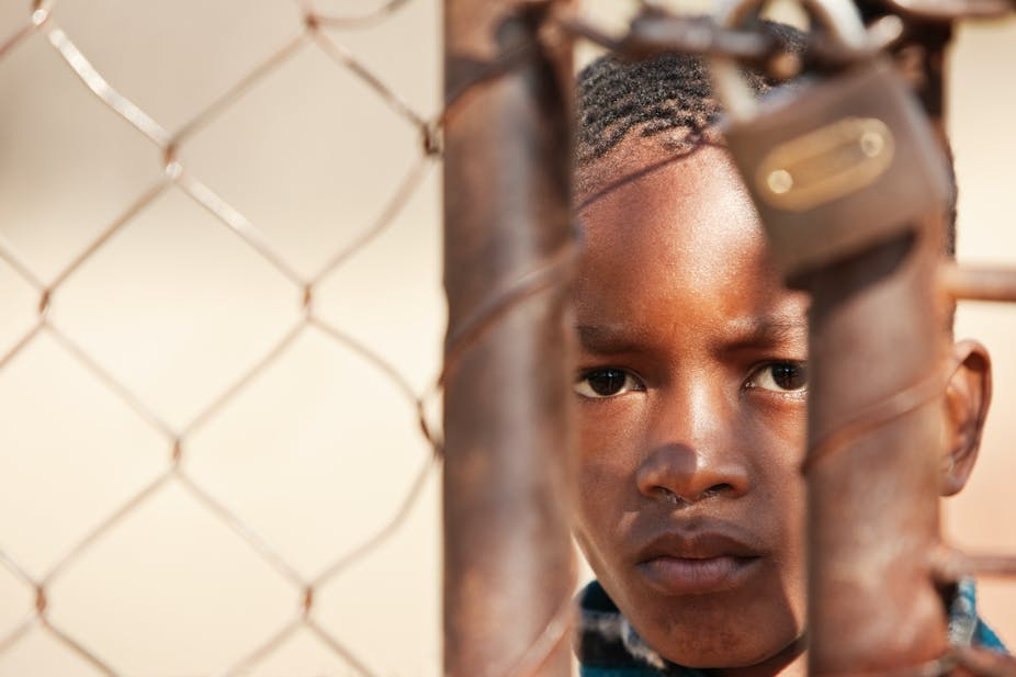 Image of a young boy looking through a closed gate