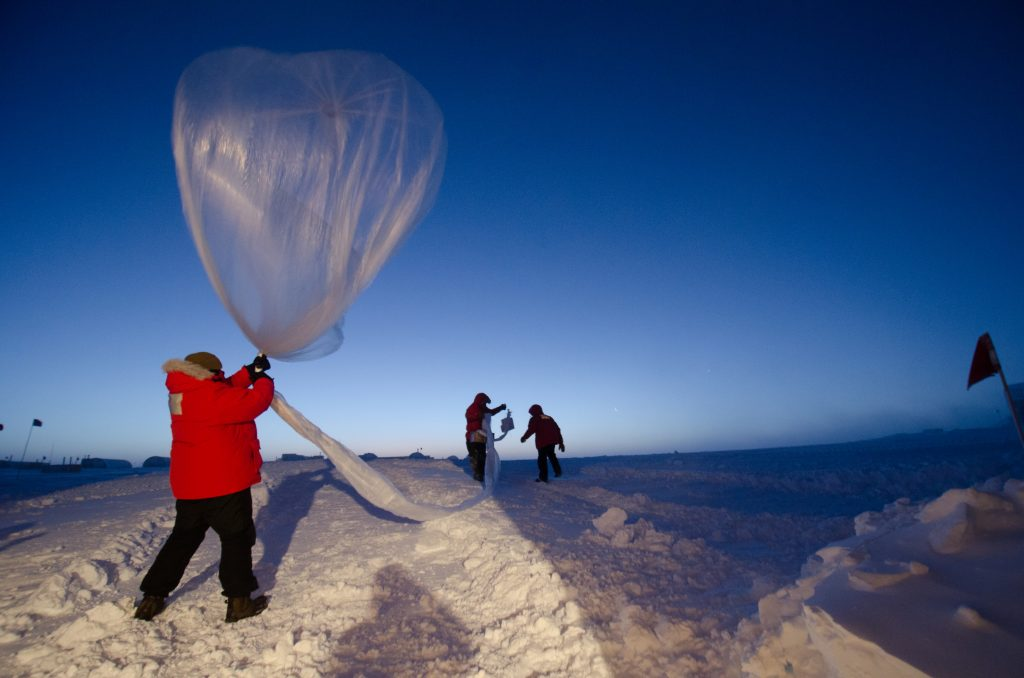 A person holding a weather balloon on top of a mountain, about to let go.