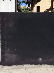Black wall paint covering the mural of an LGBTQ activist