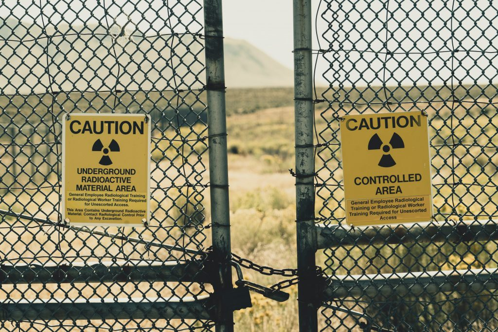 Photo of closed gate with a sign indicating caution due to radioactive material