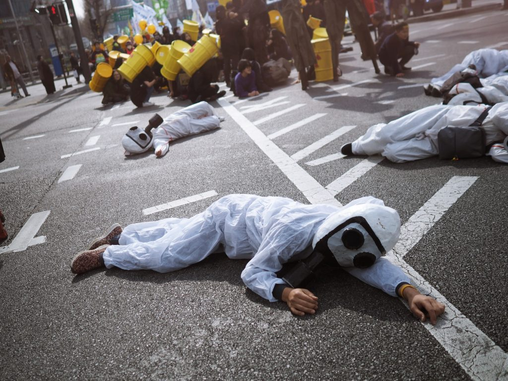 Photo of activists in nuclear protection suits laying on the ground