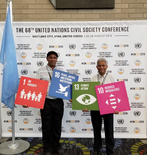 Image of two male attendees holding posters of the SDGs Numbers 1, 16, 13 and 10.