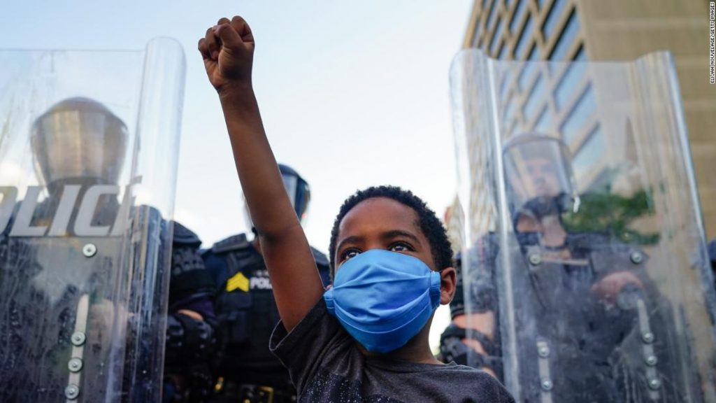 Little boy raising his fist in solidarity at a protest.
