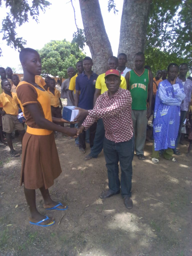 Mr Ofori, a volunteer presenting a solar reading light to a pupil at B-Zongo.