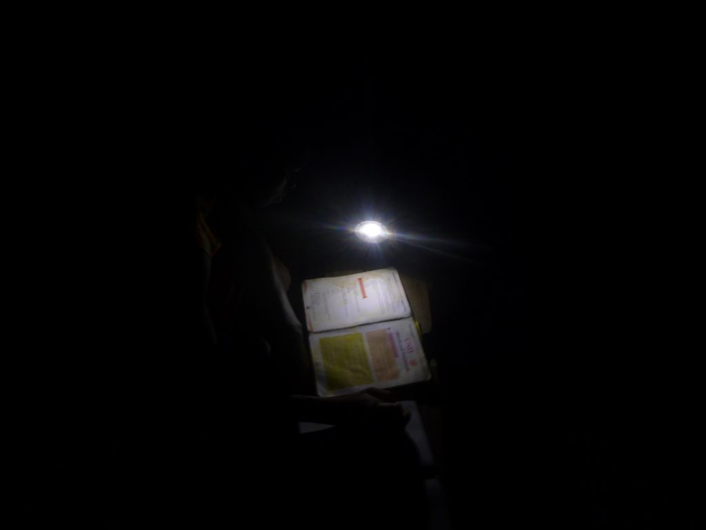 As a volunteer, I took this picture of this student learning with a solar light at night.