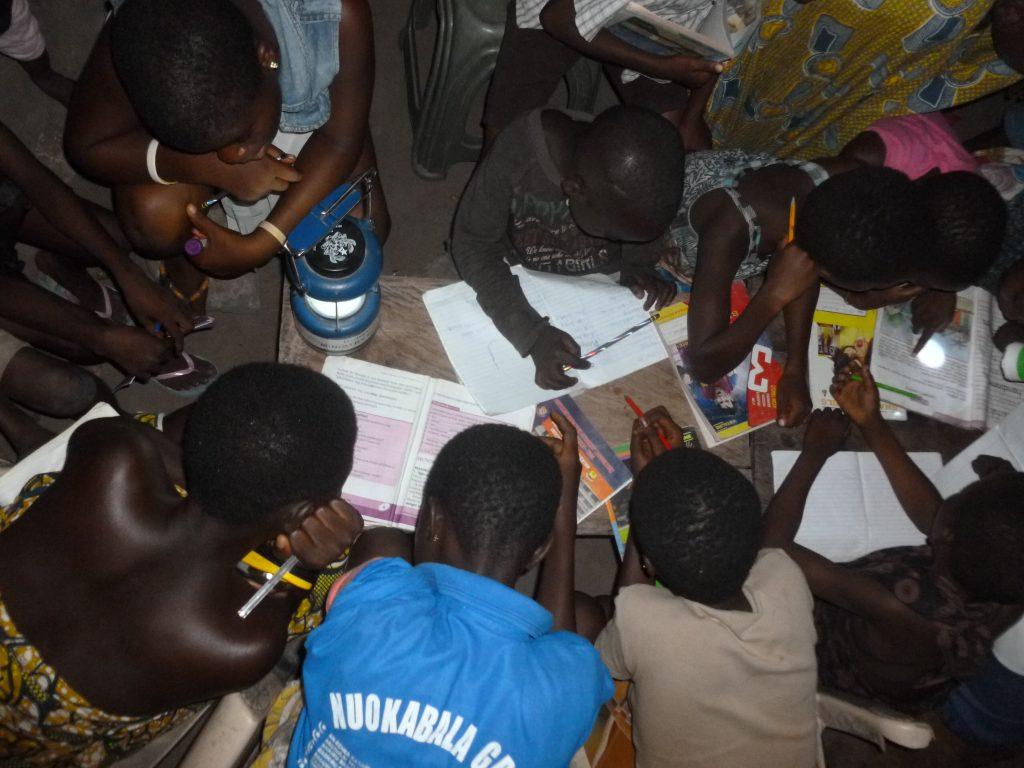 Pupils of Adaklu Dawanu, a rural  community in Ghana studying at night without electricity.