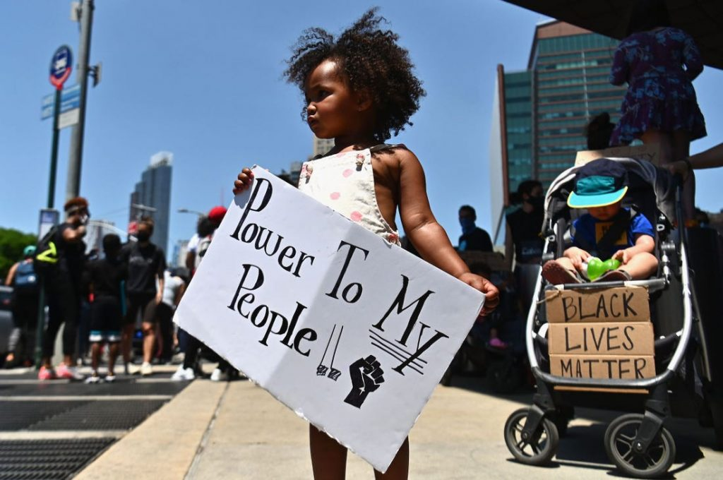 "Image of a little girl at a protest holds a sign that reads ""Power To My People."""
