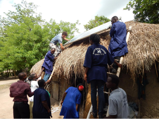 Some students of the centre undertaking a solar installation at Adaklu Gakukorpe.Julien, a volunteer from France can be seen guiding them.