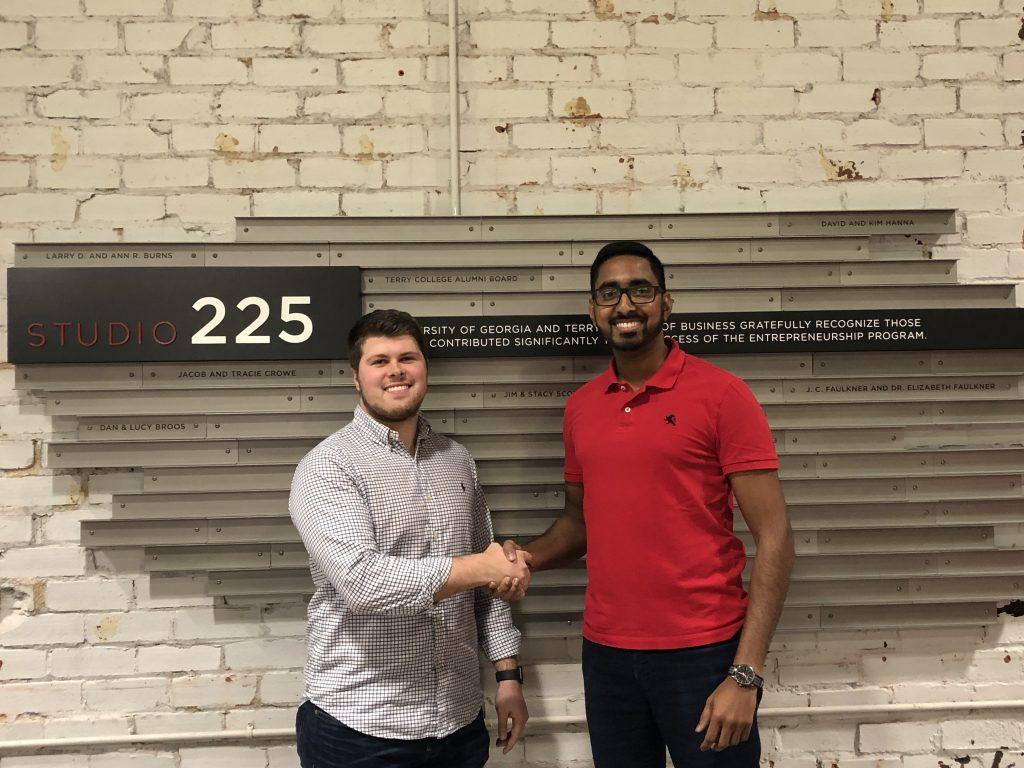 Nipuna Ambanpola (right) shaking hands with UGA Kickstarter Fund representative Casey Ridley (left) accepting $5,000 in support of IVolunteerNow.