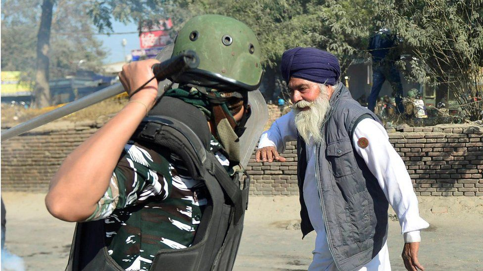 Image of an elderly Sikh man (probably a farmer) and police officer with his baton raised about to hit the man