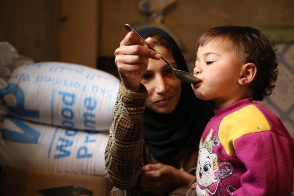 Image of a  woman feeding a child.