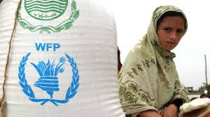 Image of a young girl sits next to a bag stamped with the WFP logo