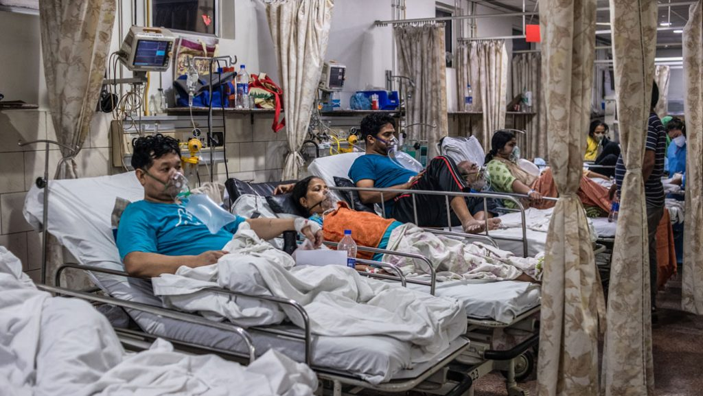 Hospital beds filled with Covid-19 patients wearing oxygen masks.