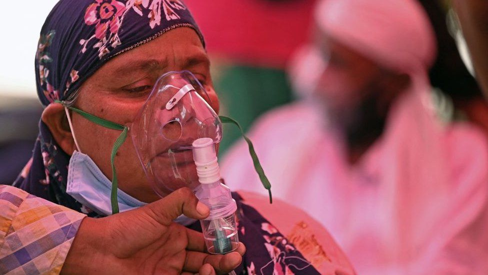 An image of an oxygen mask being placed on a woman.