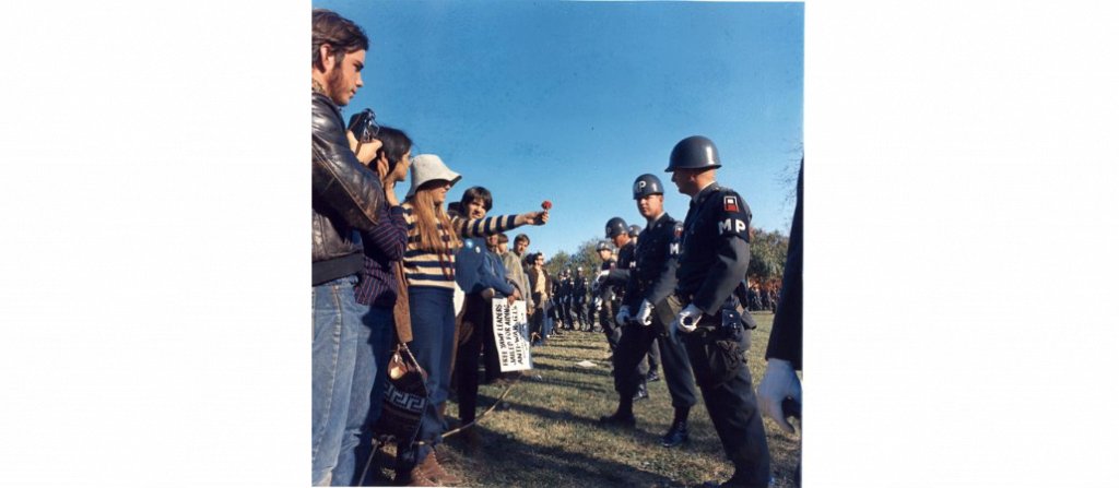 Photograph of a Female Demonstrator Offering a Flower to a Military Police Officer