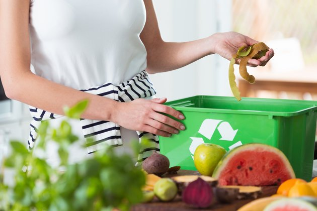 Image of a woman throwing decomposable food waste into a recycle bin.