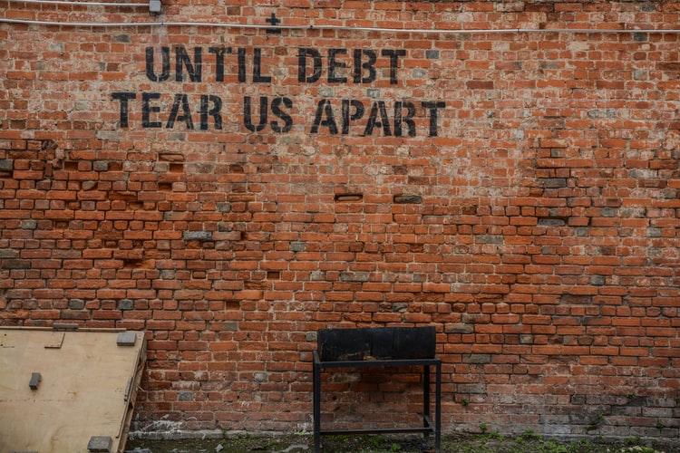 "Image of a graffiti saying ""until debt tear us apart"""