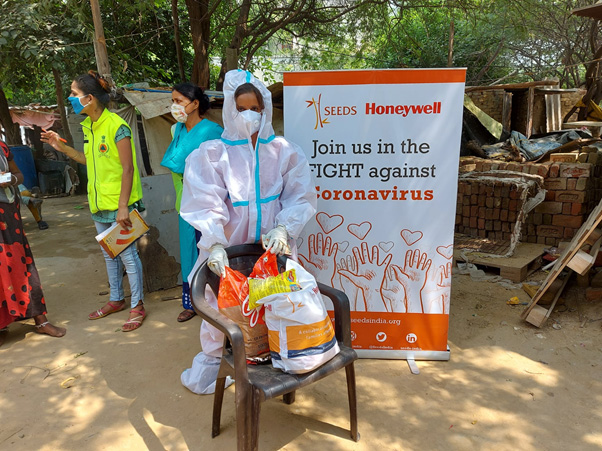 Women wearing masks and PPE kits near a SEEDS India banner.