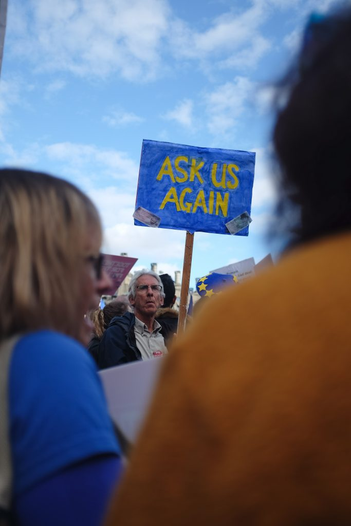 An abstract image of a man holding a poster reading 'Ask us again' in the context of Brexit
