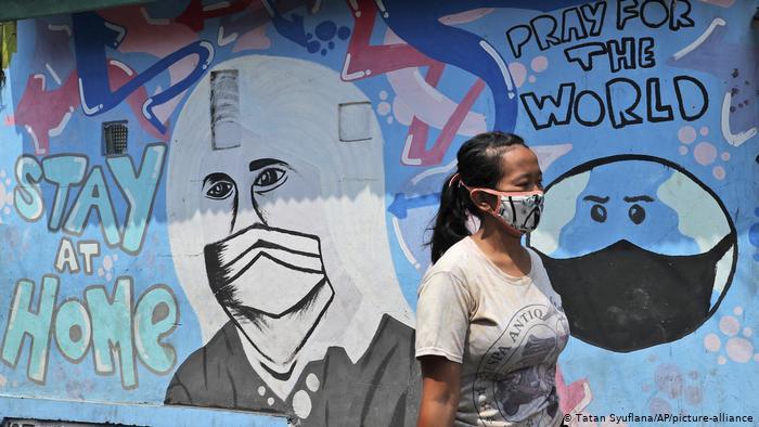 Woman walking past a Covid-19 mural.