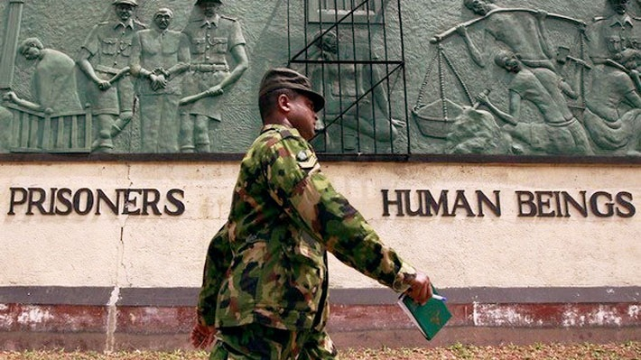 An image of a Sri Lankan soldier walking past the front wall of the Welikada prison which reads 'Prisoners are human beings'