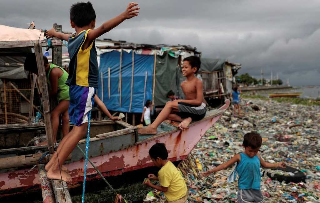 Children playing on a boat docked near a pile of garbage.