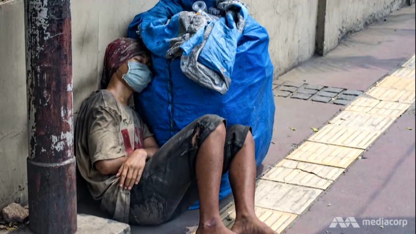 A man wearing a mask and torn clothes is resting on a sidewalk.