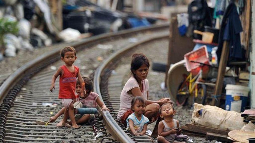 A woman and children sitting on a railway track near slums in Indonesia.