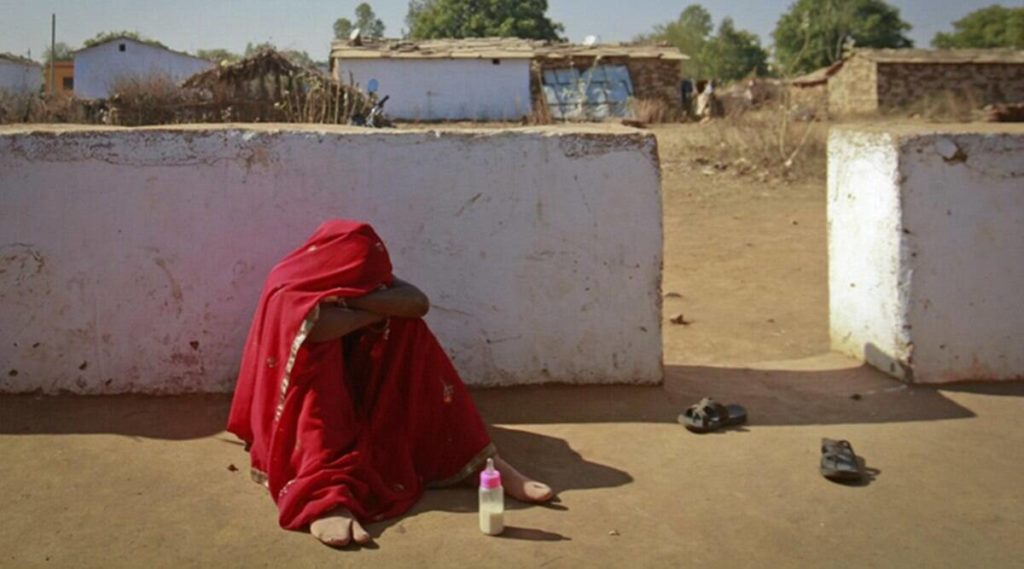 A barefooted girl sadly sitting on floor with a child feeder and poor surrounding.