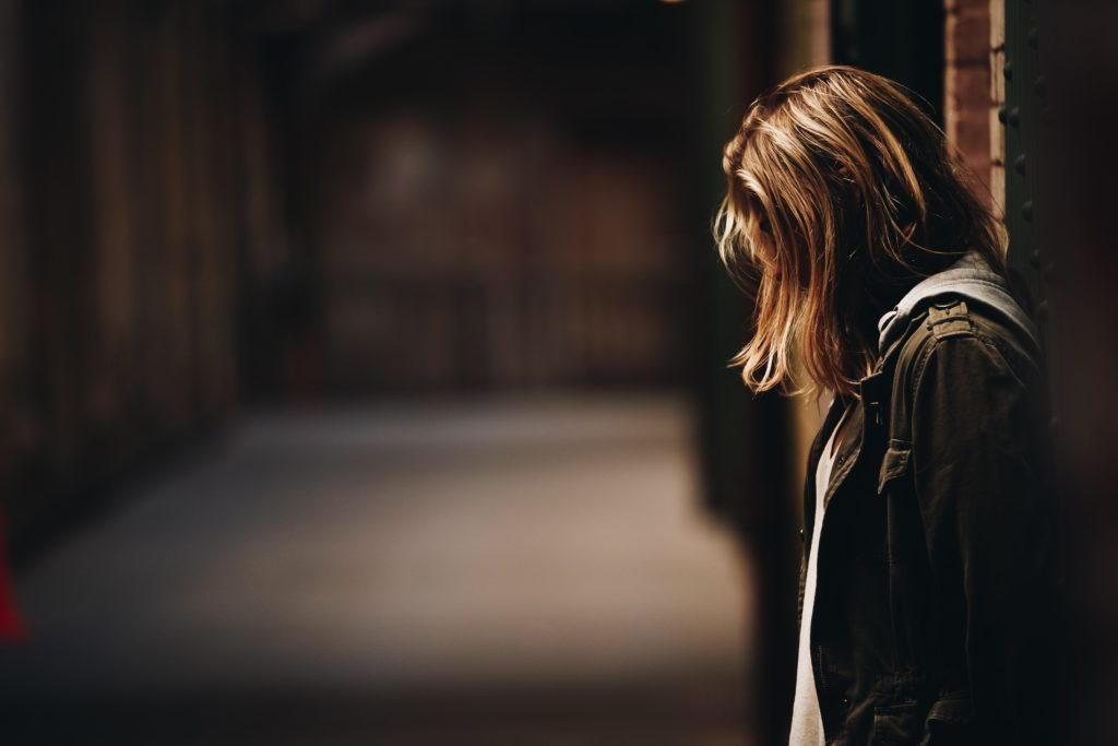 An image of a girl standing isolated and distressed.