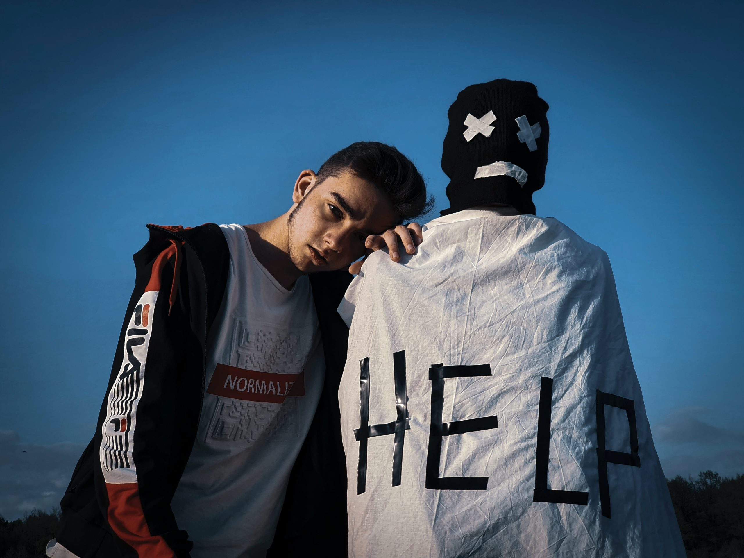 Image of a teen standing beside the physical manifestation of his mental illness, seeking out for help.