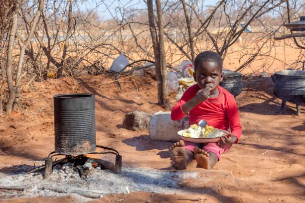 african child in a village near Kalahari desert, in the outdoors kitchen